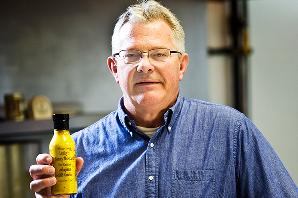 a photo of Mark Porisch holding a bottle of Lucky's Popcorn Dressing