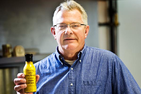 a photo of Mark Porisch holding a bottle of Lucky's Popcorn Dressing