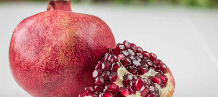a photo of a ripe pomegranate and seeds on a table