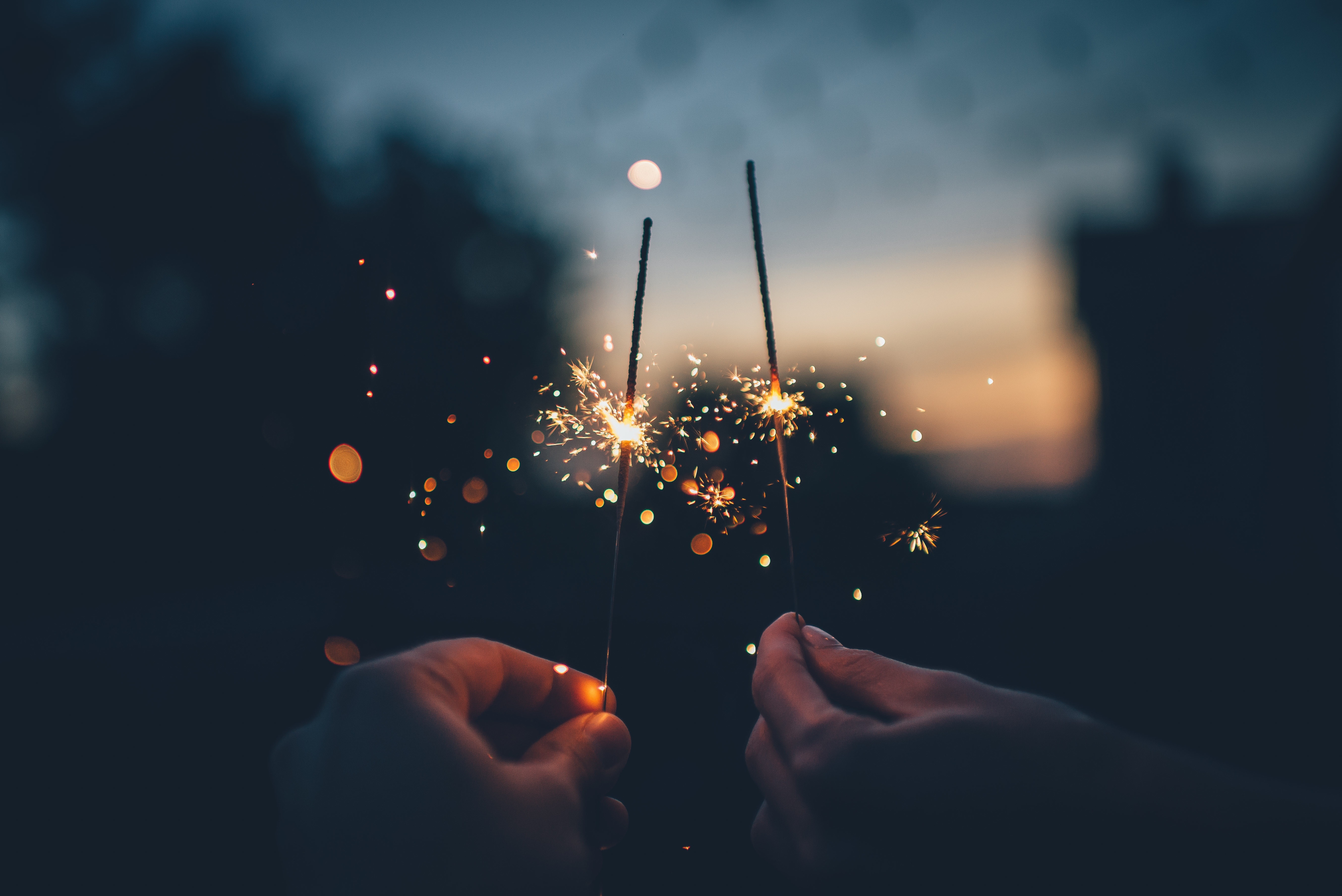 a photo of two hands holding sparklers