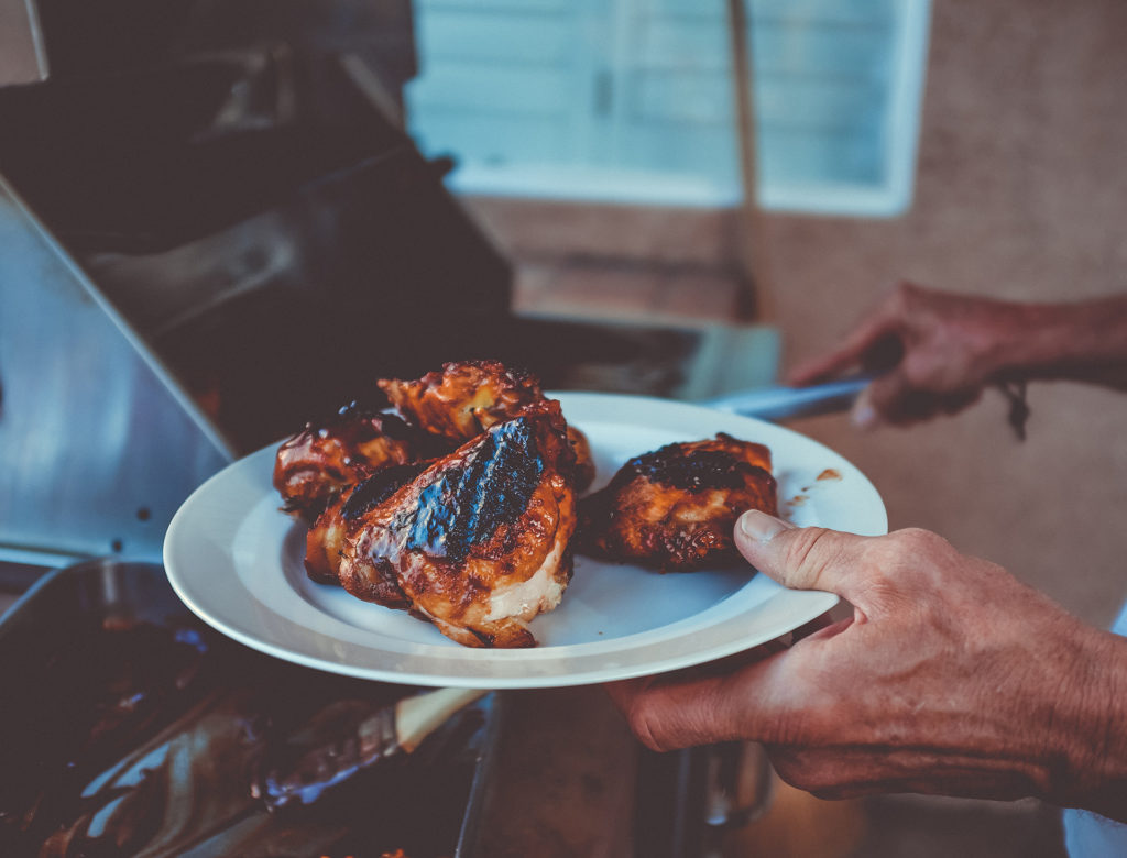 a photo of someone grilling chicken