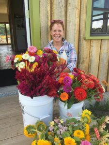 a photo of Jenny with her flowers at Little Big Sky Farm