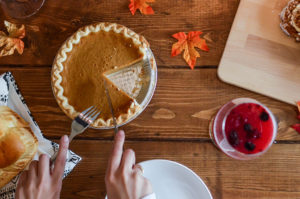 a photo of two hands cutting into a punpkin pie