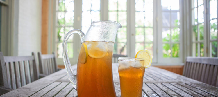 a photo of iced tea in a glass and pitcher sitting on a table