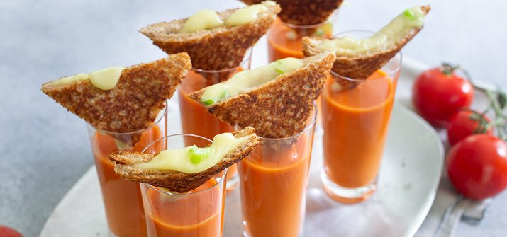 A photo of six shooters of orange tomato soup with triangled of grilled cheese set on top of each.