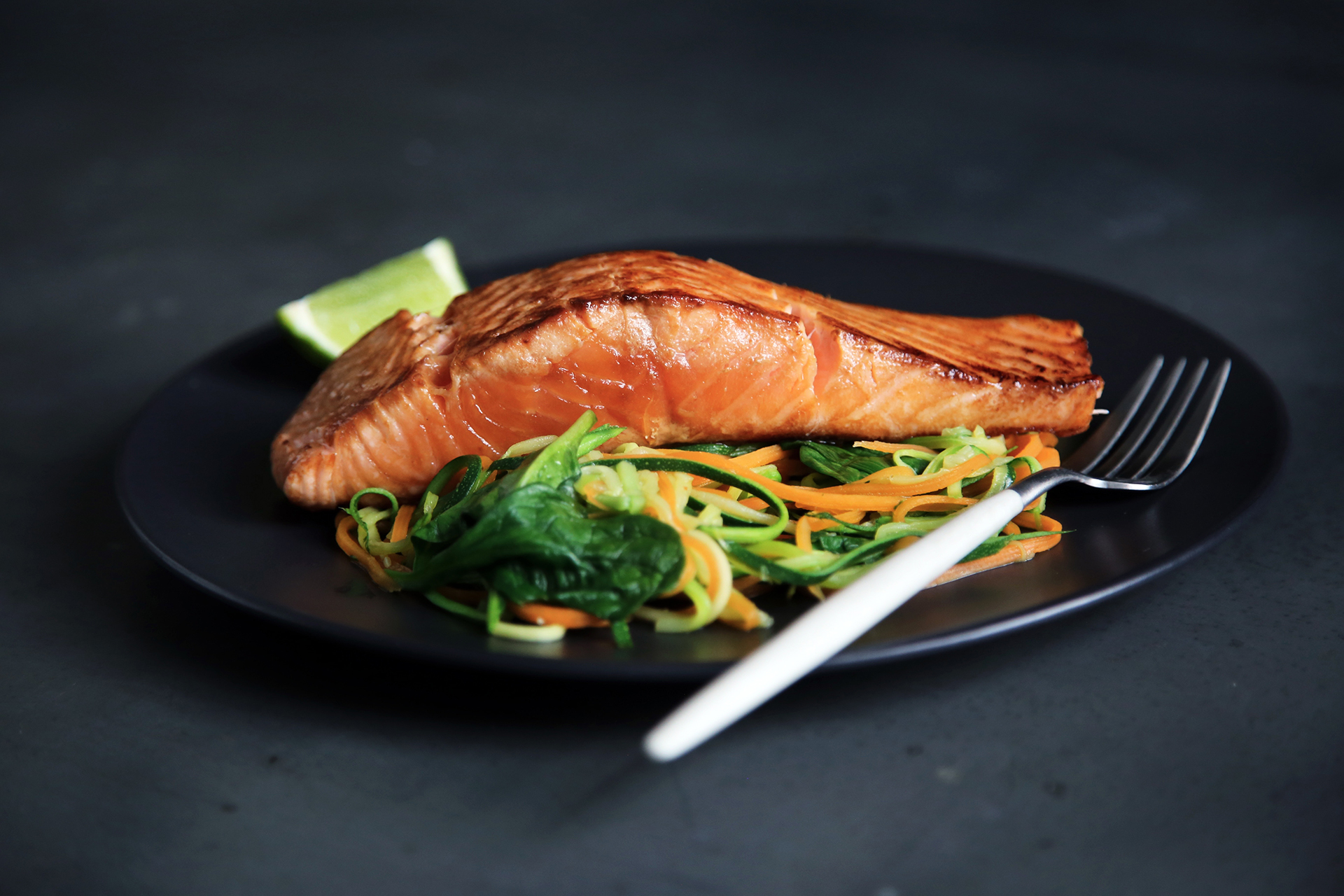 a photo of a black plate with a fork, a piece of cooked salmon, and vegetables