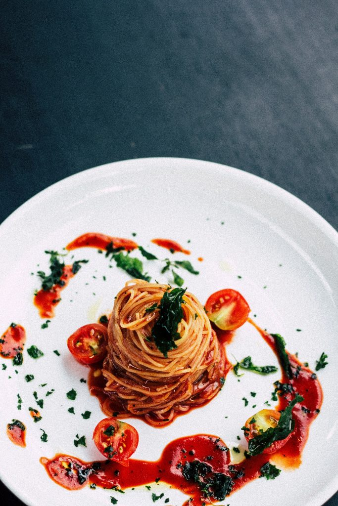 a photo of a white plate with a pile of pasta in the center with red sauce and tomatoes