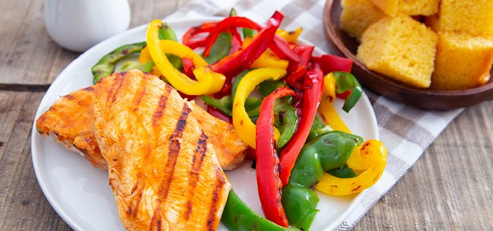 A photo of grilled chicken on a plate with a side of red, green, and yellow bell peppers