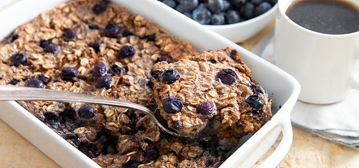 A photo of a dish full of banana berry baked oats with a spoon in it and a cup of coffee