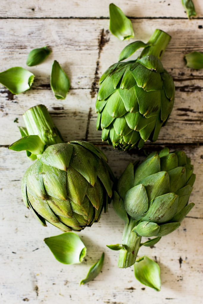 a photo of three green artichokes on a table