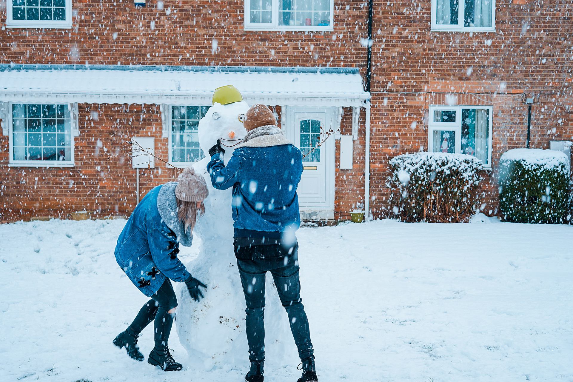 a photo of two people building a snowman in front of a brick structure