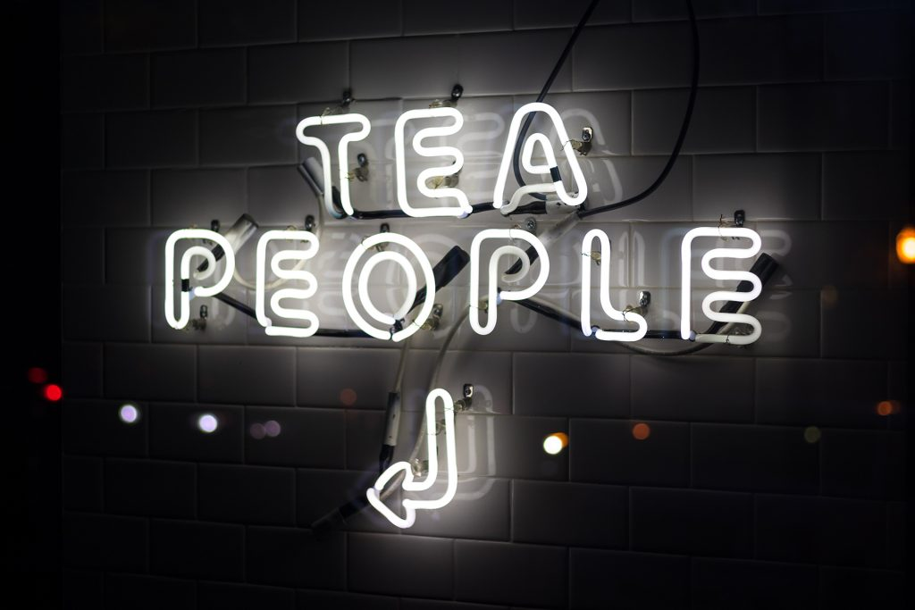 a photo of a neon sign that says tea people with an arrow pointing to the left