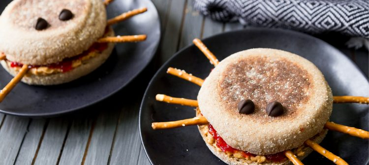 a photo of peanut butter and jelly spider sandwichest on black plates