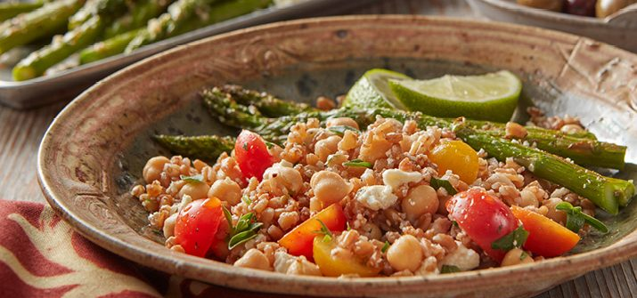 Mediterranean Farro Salad in a dish served with asparagus and lime