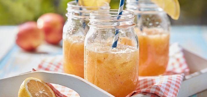 Three mason jars with lemon garnishes and paper straws